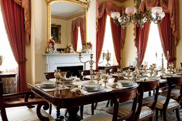 Elegant dining room that's well-lit with windows and red curtains, has long, dark wooden dining table that is fully set, and has a white fireplace