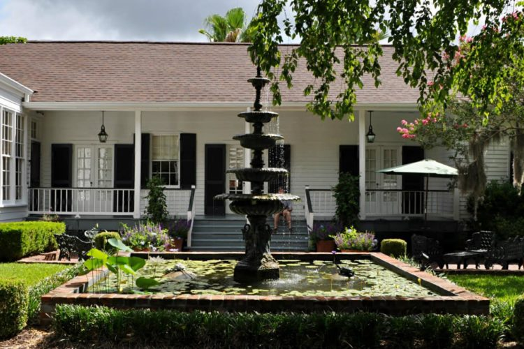 Large fountain with red brick border and green lilypads sitting in front of white colonial house with black shutters