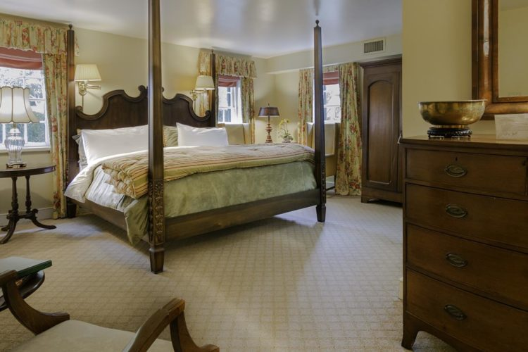 Large bedroom decorated with king-sized bed with tall dark bedposts, white, green, and striped linens; walls are eggshell colored, cream carpeting, and dark wood furniture