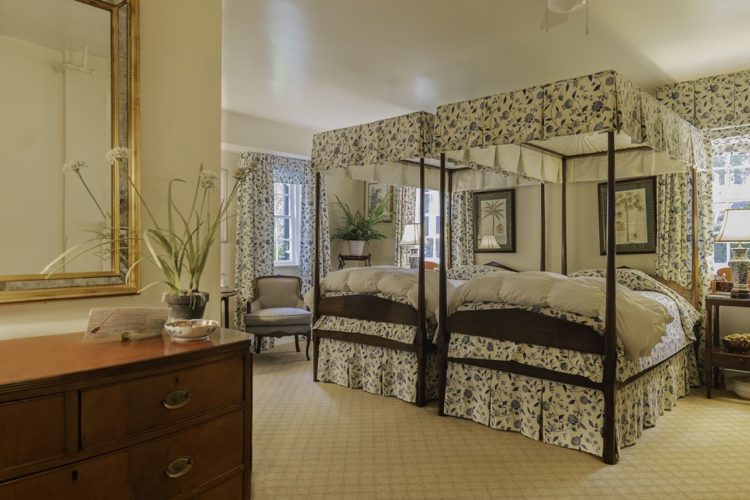 Twin bedroom with two identical poster beds with white and blue flower print, cream carpeting and walls, bright windows, and wooden wardrobe and dresser