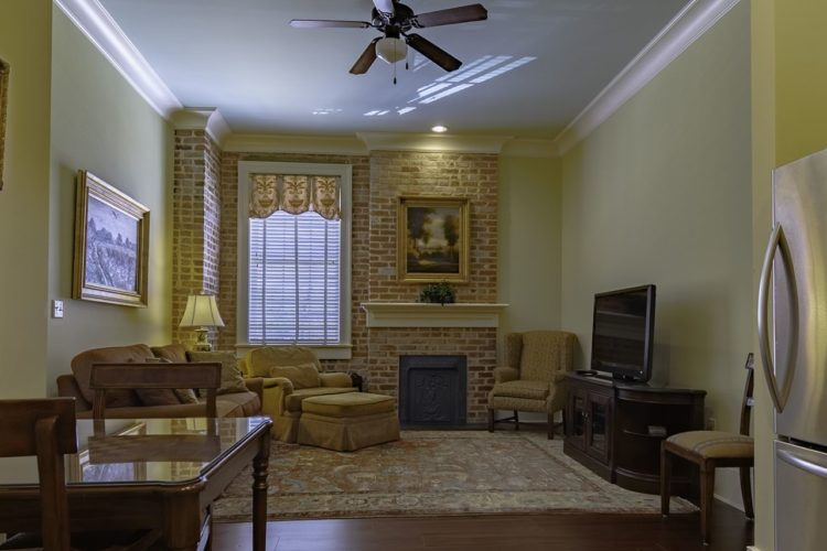 Living room area viewed from kitchen; walls are pale yellow, brick fireplace with large window, yellow and brown furniture, and flatscreen tv