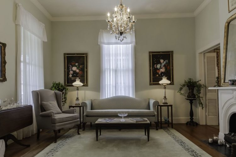 Neat living room area with cream walls, dark wood flooring and cream carpet, light gray furniture, flower paintings, and white fireplace with small coffee table