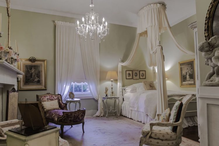 Large cream and white bedroom with fireplace to the left, purple decorative fainting chair, white bed with canopy, and crystal chandelier