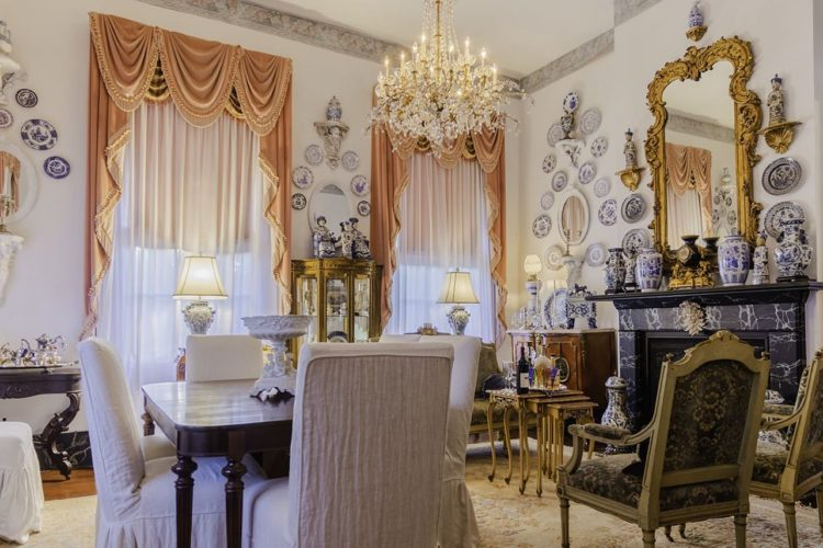Decorative sitting area and dining room with large windows, white cast-iron stove, black marbled fireplace, crystal chandelier, and porecelain plates and vases decorating the walls