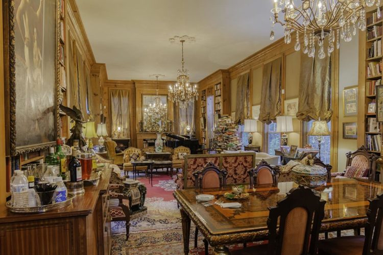 Large personal library room and dining area that is full of warm colors, wooden shelves, victorian furniture, windows, chandeliers, piano, and case of alcohols.