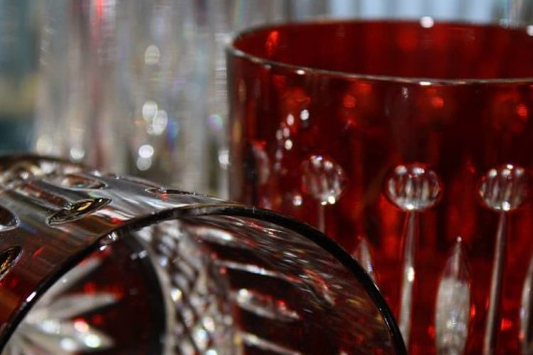 Close-up of drinkware; two red glass cups with intricate designs along the sides and clear glasses in blurry background