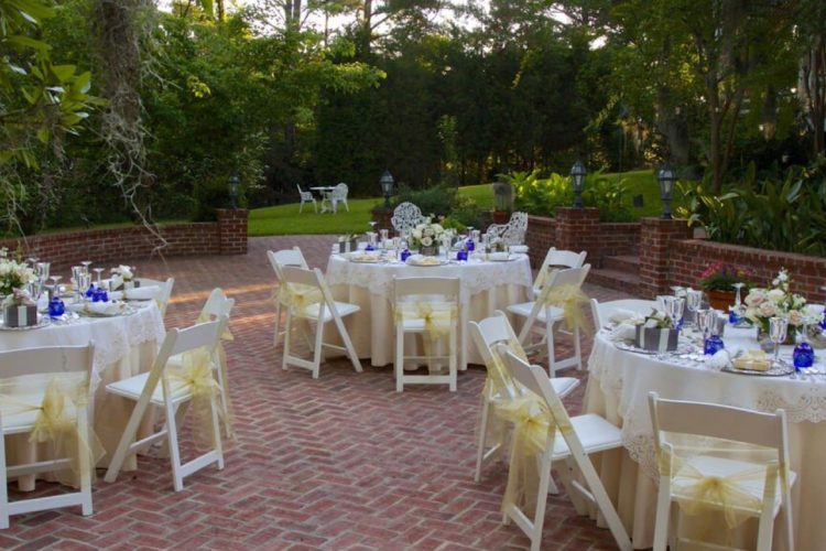 Back porch inlayed with red brick readied for a wedding reception with three white tables and chairs with yellow bows. Tables filled with glassware and bright green trees line backyard
