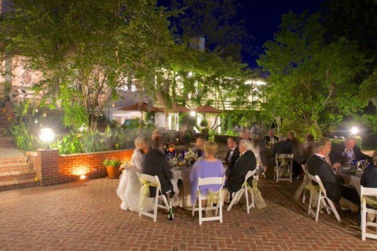 Wedding reception held on large, red brick porch area with guests sitting in white chairs surrounded by green trees and bright lighting after the sun has set