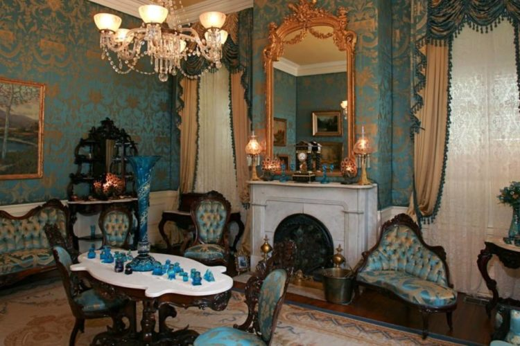 Victorian-inspired room filled with turquoise and gold accents and intricate wallpaper, victorian lounge furniture, blue glass vases, with marble fireplace, small lamps, and crystal chandelier