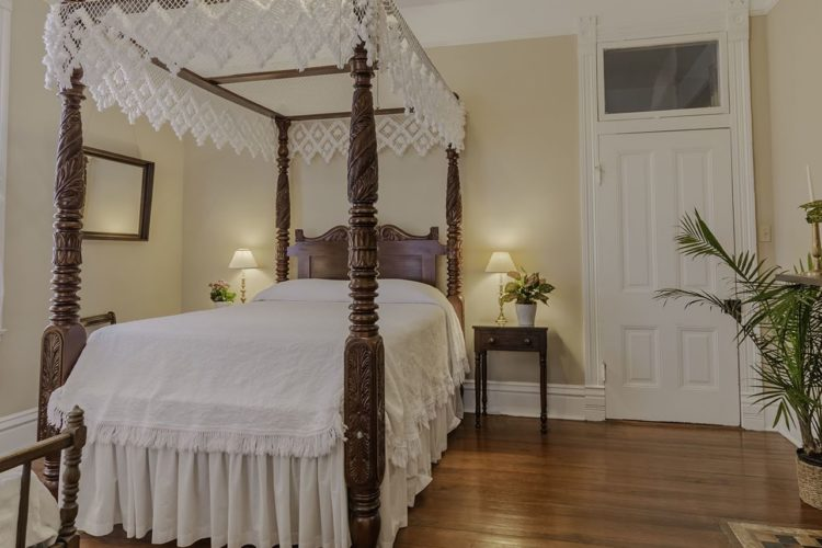 Twin bedroom depicting a poster bed with dark wooden posts, cream walls, wood flooring, white door, and a rustic fireplace with a bright window