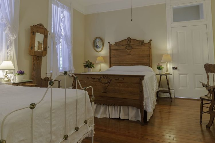 A bedroom with two beds, one with a white metal bedframe and one with a rustic wooden bedframe and headboard, wood flooring, cream walls, and a small table set