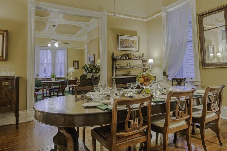 A dining area decorated with a long wood table with six chairs, cream walls, wood panel flooring, and a wooden alcohol cabinet