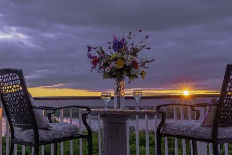 Outdoor porch setting with two chairs, marble-topped table with perky flower vase and wine glasses overlooking the water and yellow sunset with light cloud cover